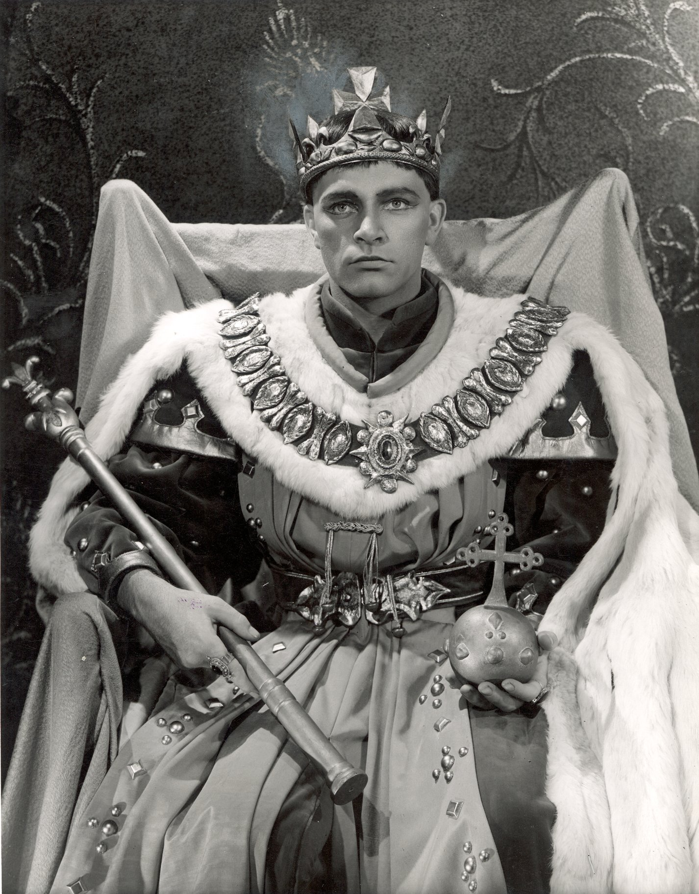 Richard Burton as Henry V sits in his throne dressed in ceremonial robes with sceptre and orb, wearing a crown, in the 1951 production of Henry V
