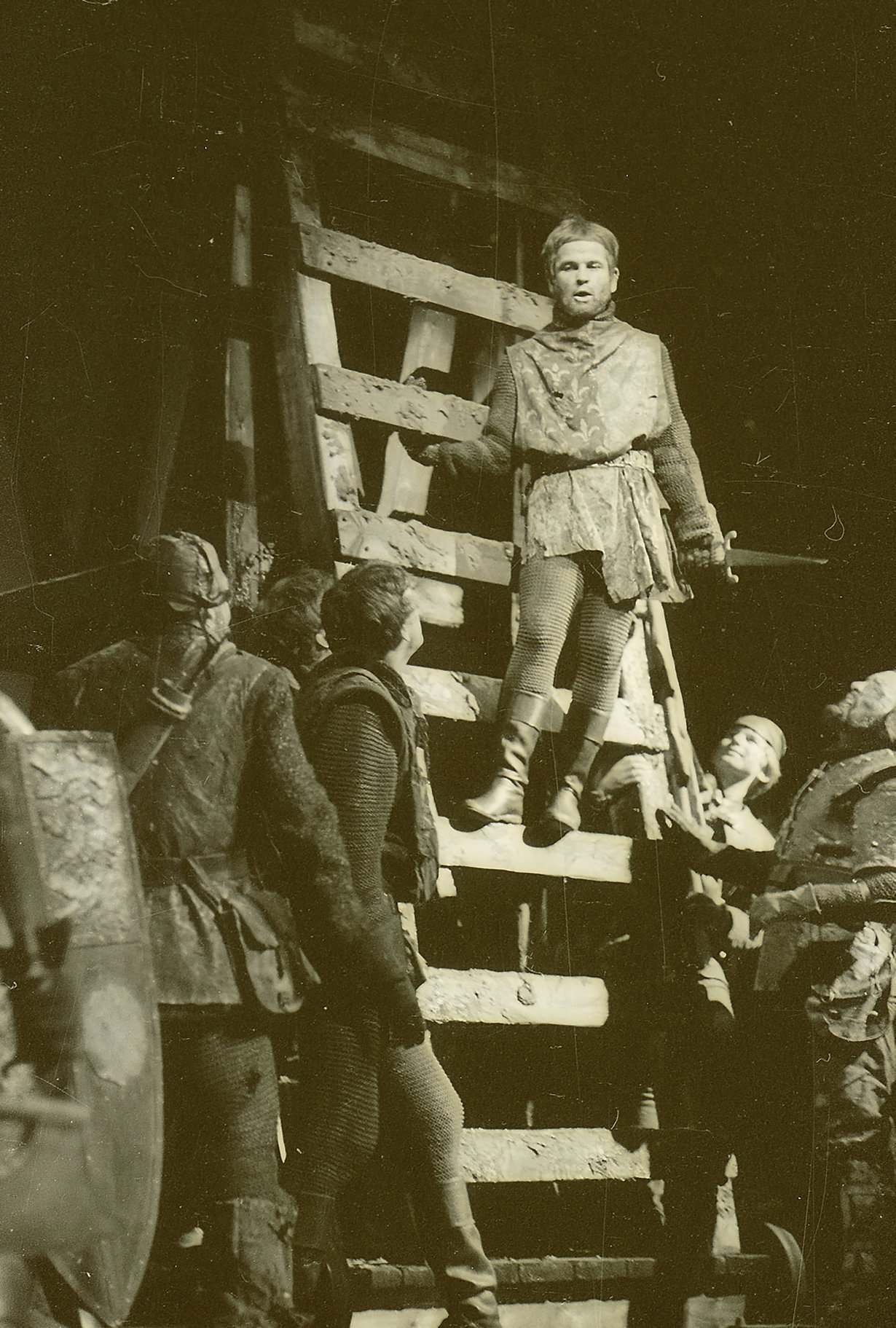 Henry stands on a large wooden ladder looking down on his troops and rallies his men in the 1964 production of Henry V