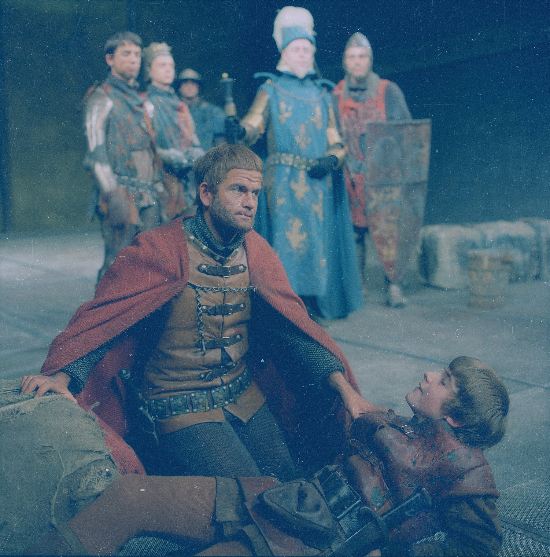Henry clutches the shoulder of the Boy as he lies on the ground, dying, in the 1965 production of Henry V