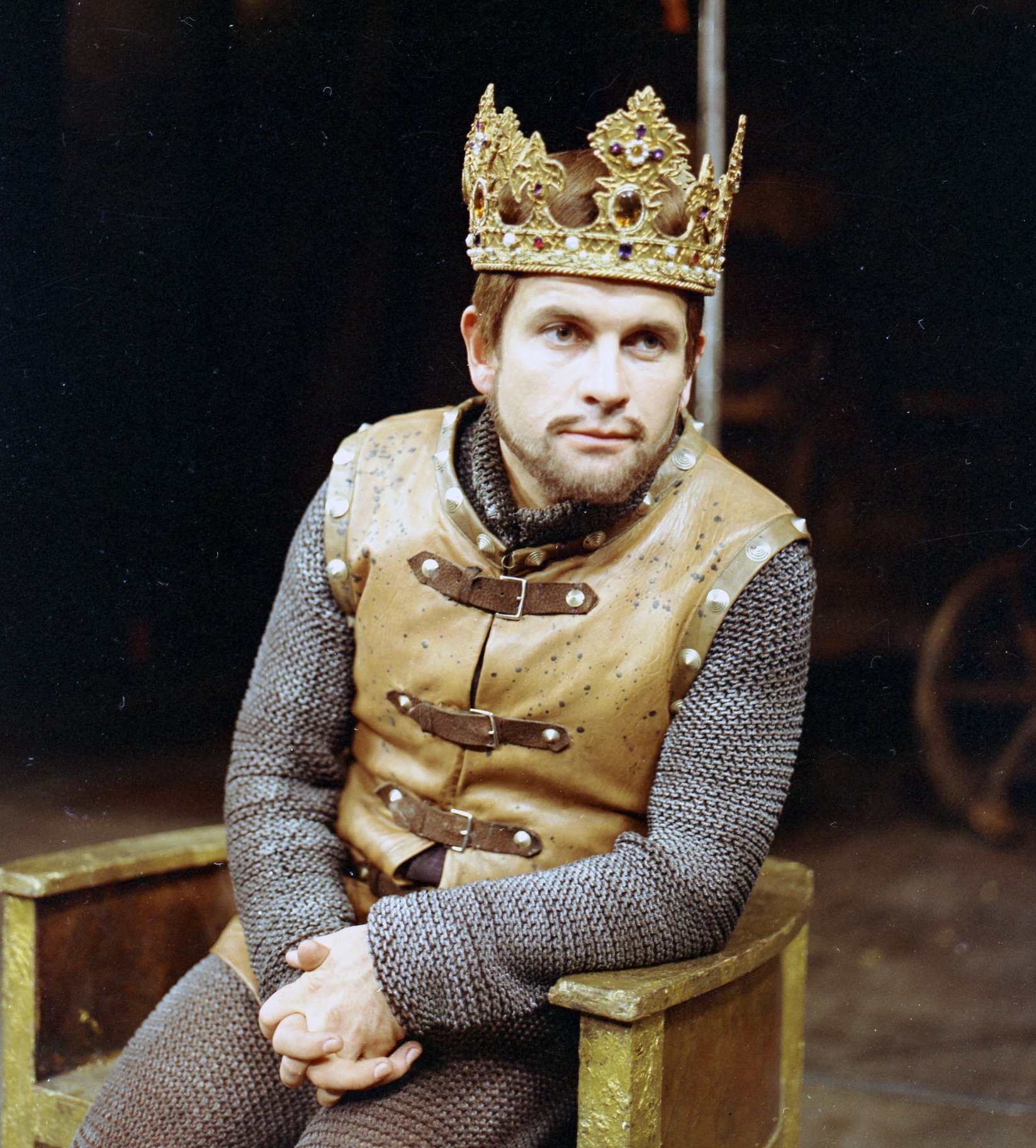 Ian Holm as Henry wears chain mail and a crown sitting in a wooden throne in the 1965 production of Henry V