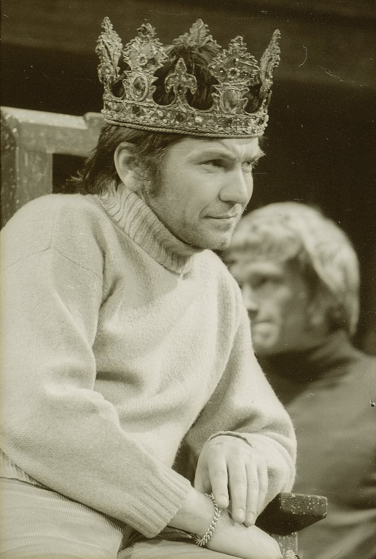 Michael Williams as Henry V, wears a casual jumper and crown, leaning on the arm of the wooden throne he is sitting in, in the 1971 production of Henry V