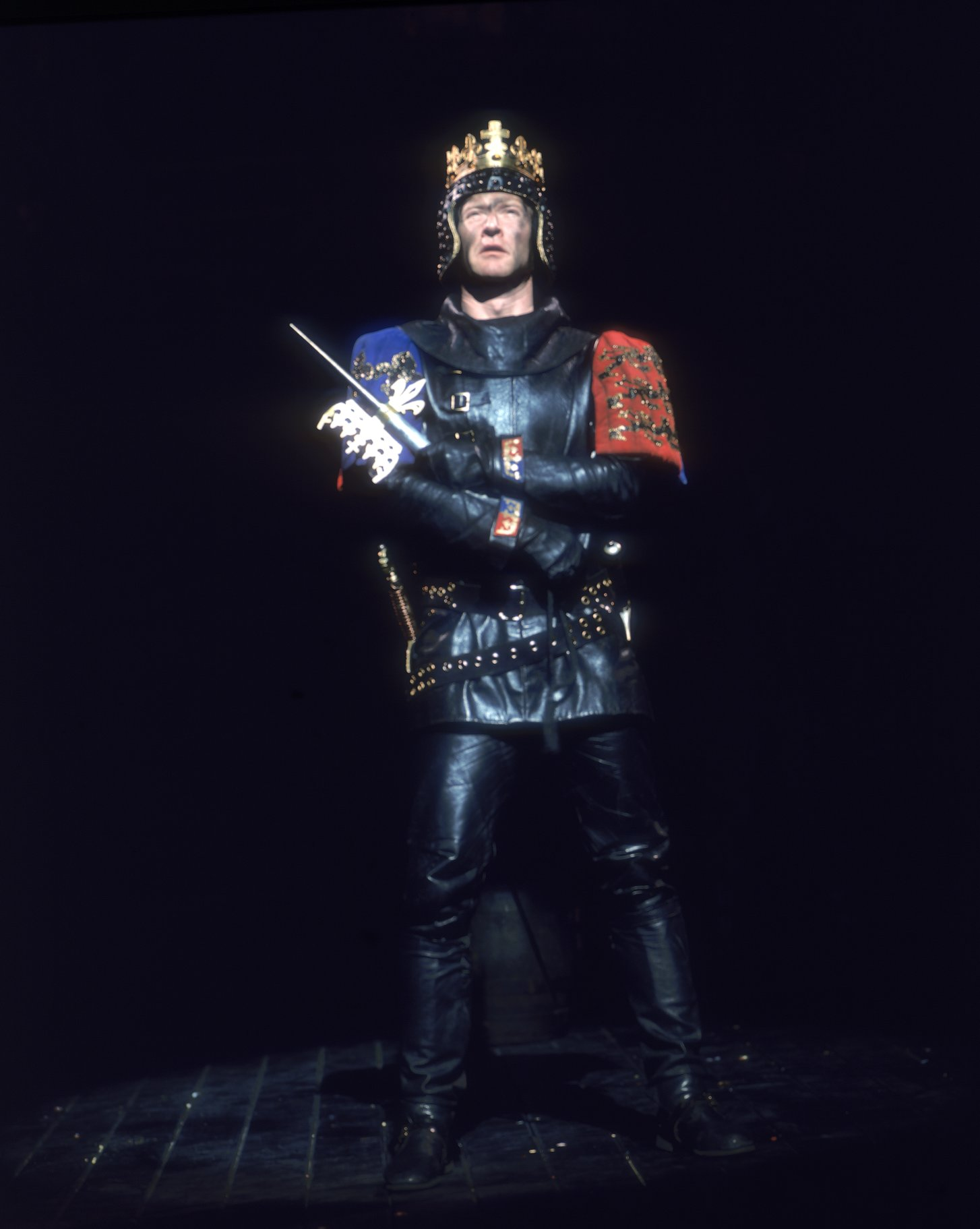 Henry V wears full body armour and holds his sword over one shoulder in the 1975 production of Henry V
