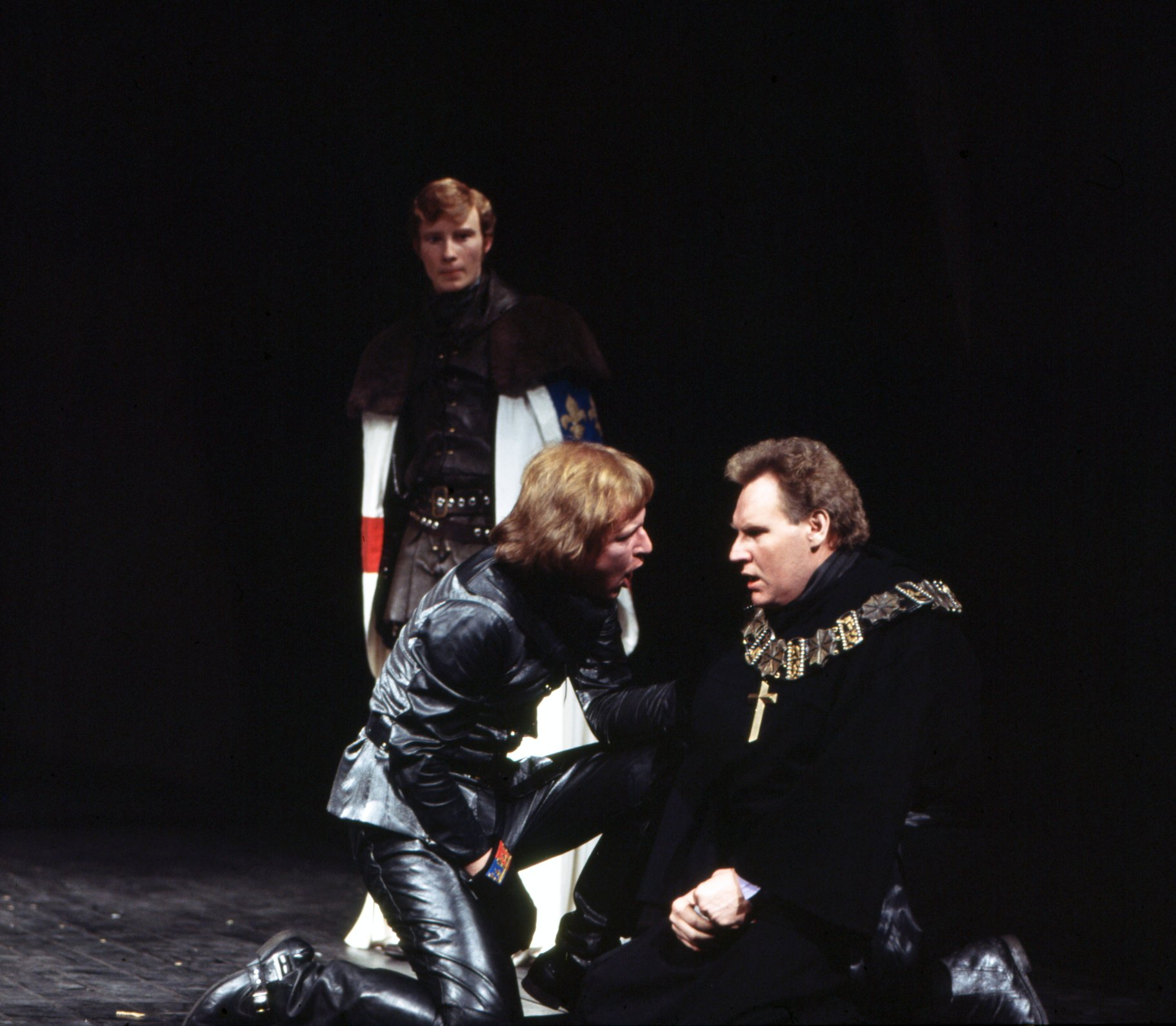 Henry kneels down to shout at a collapsed Scroop, who sits with his hands in his lap on the floor in the 1975 production of Henry V