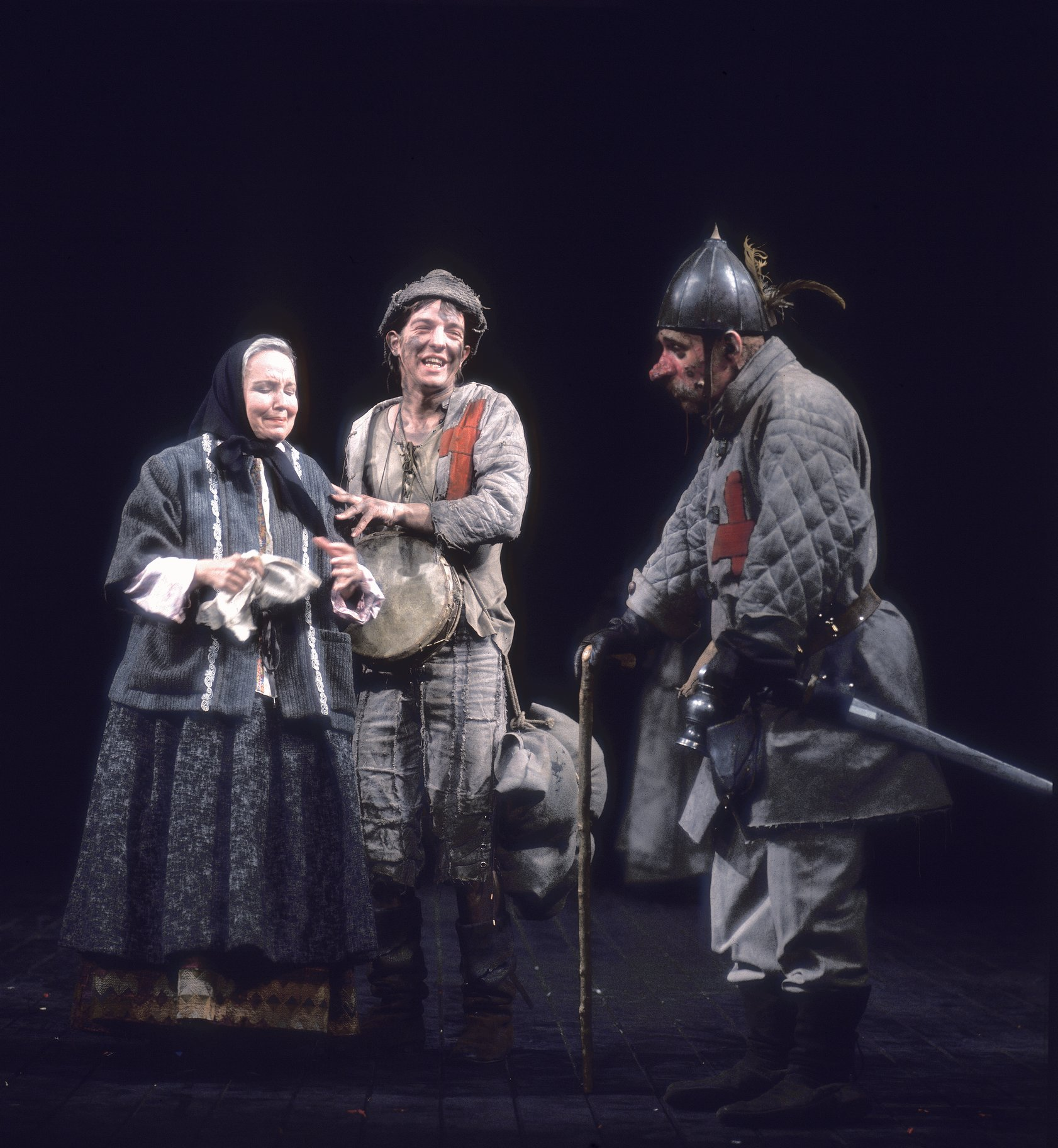 Mistress Quickly and the Boy laugh at a miserable looking Bardolph, as he leans on his cane, in the 1975 production of Henry V
