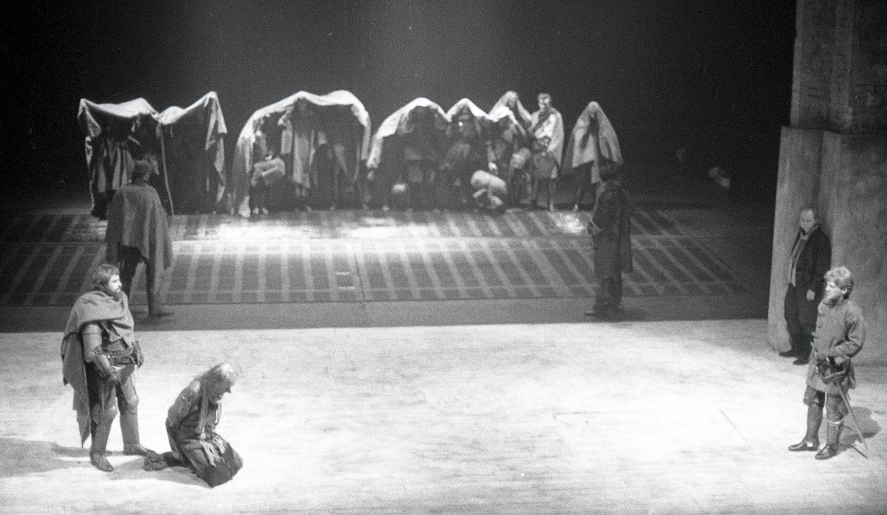 Bardolph kneels before the king to receive his punishment as other offenders are lined up at the back of the stage in the 1984 production of Henry V
