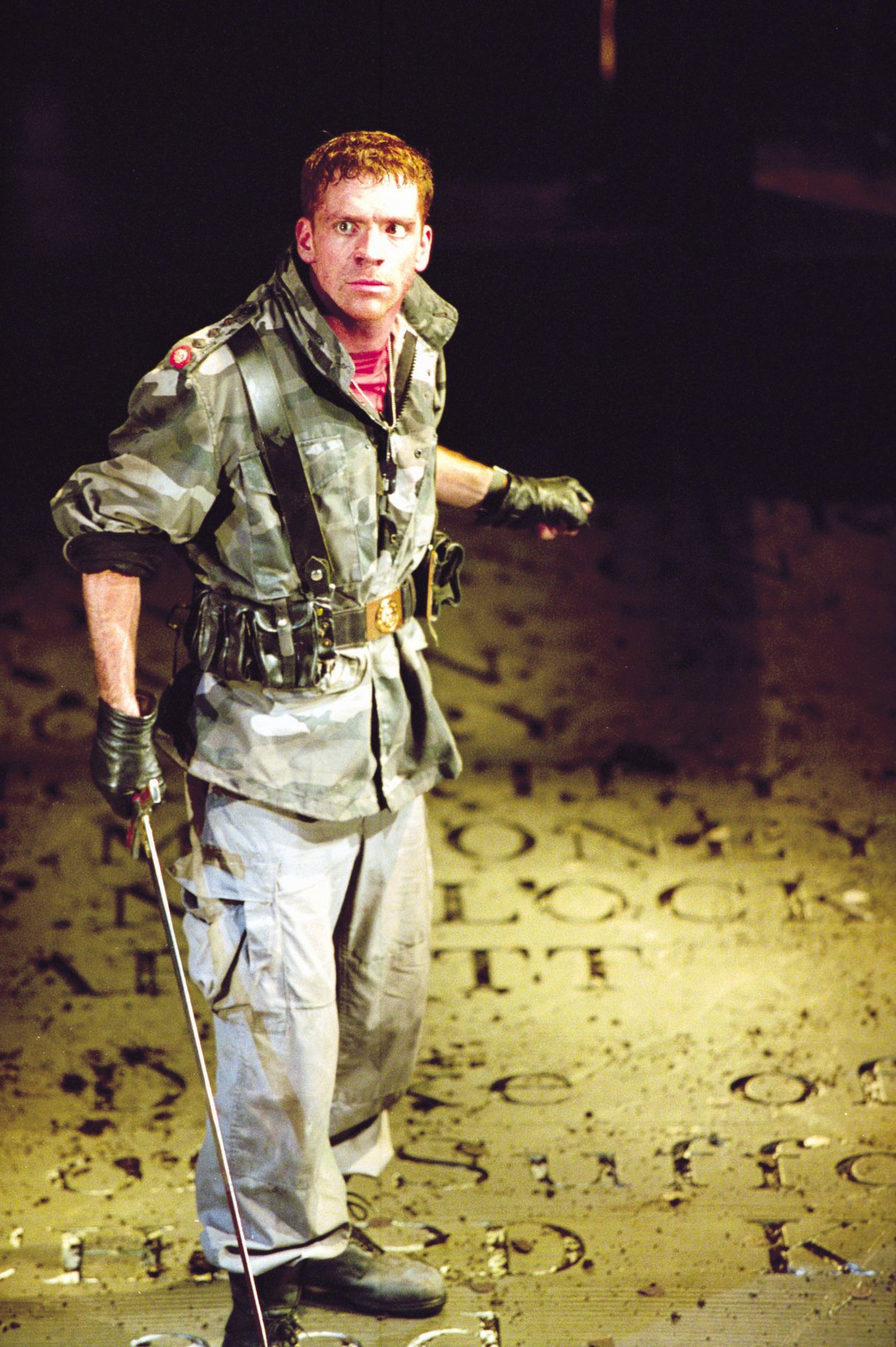 Henry dressed in camouflage and khakis holds a sword in battle in the 2000 production of Henry V