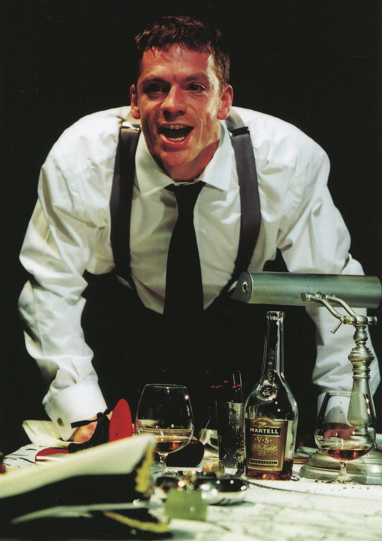 William Houston as Henry V leans on a table covered in drinks and bottles, shouting, in the 2000 production of Henry V