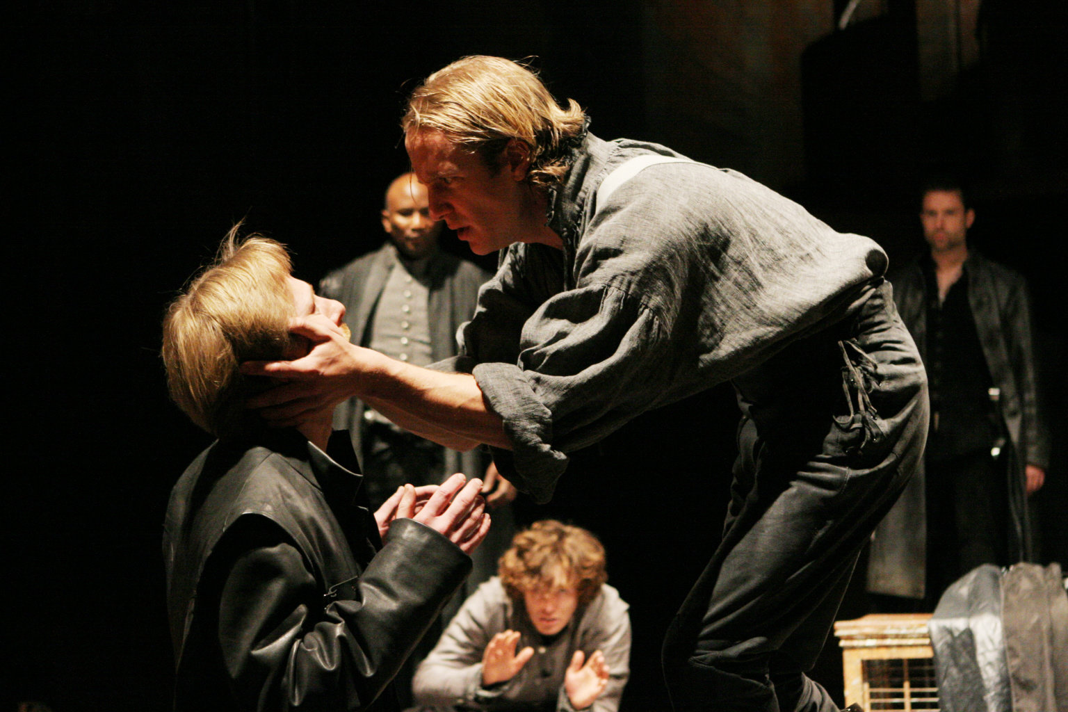 Henry holds Scroop's head with both hands as he questions him in the 2007 production of Henry V