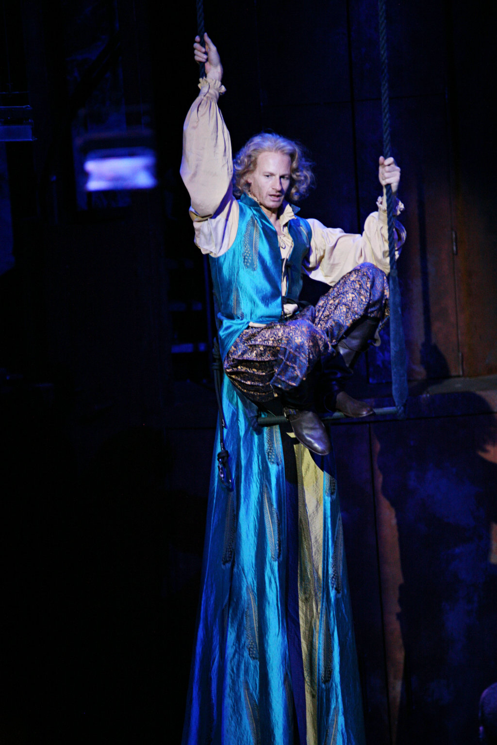 The Dauphin, dressed in long blue silk robes, hangs from the ceiling on a trapeze, looking down in the 2007 production of Henry V
