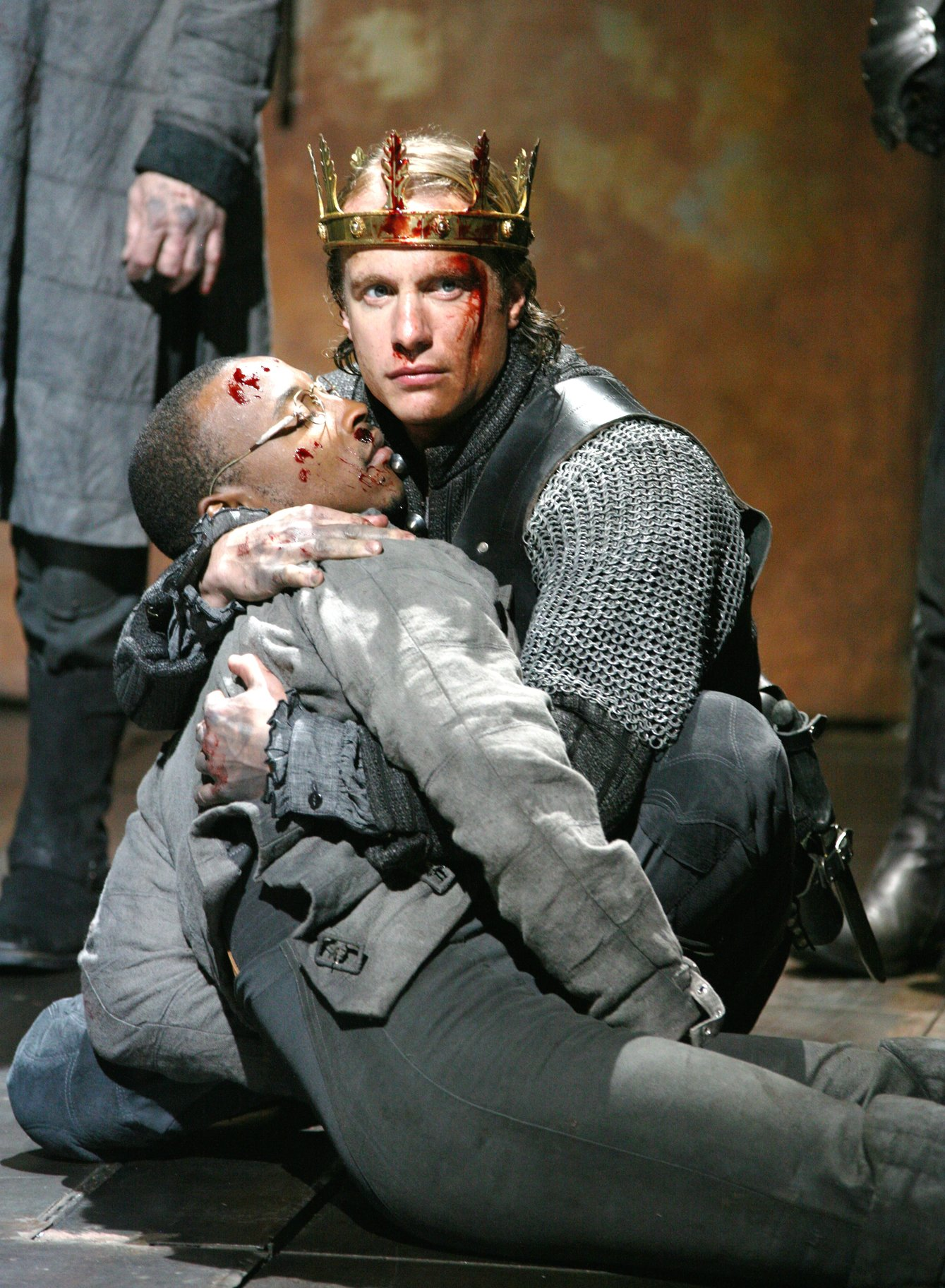 Henry clutches at the Boy, holding him as he dies, both covered in blood in the 2007 production of Henry V