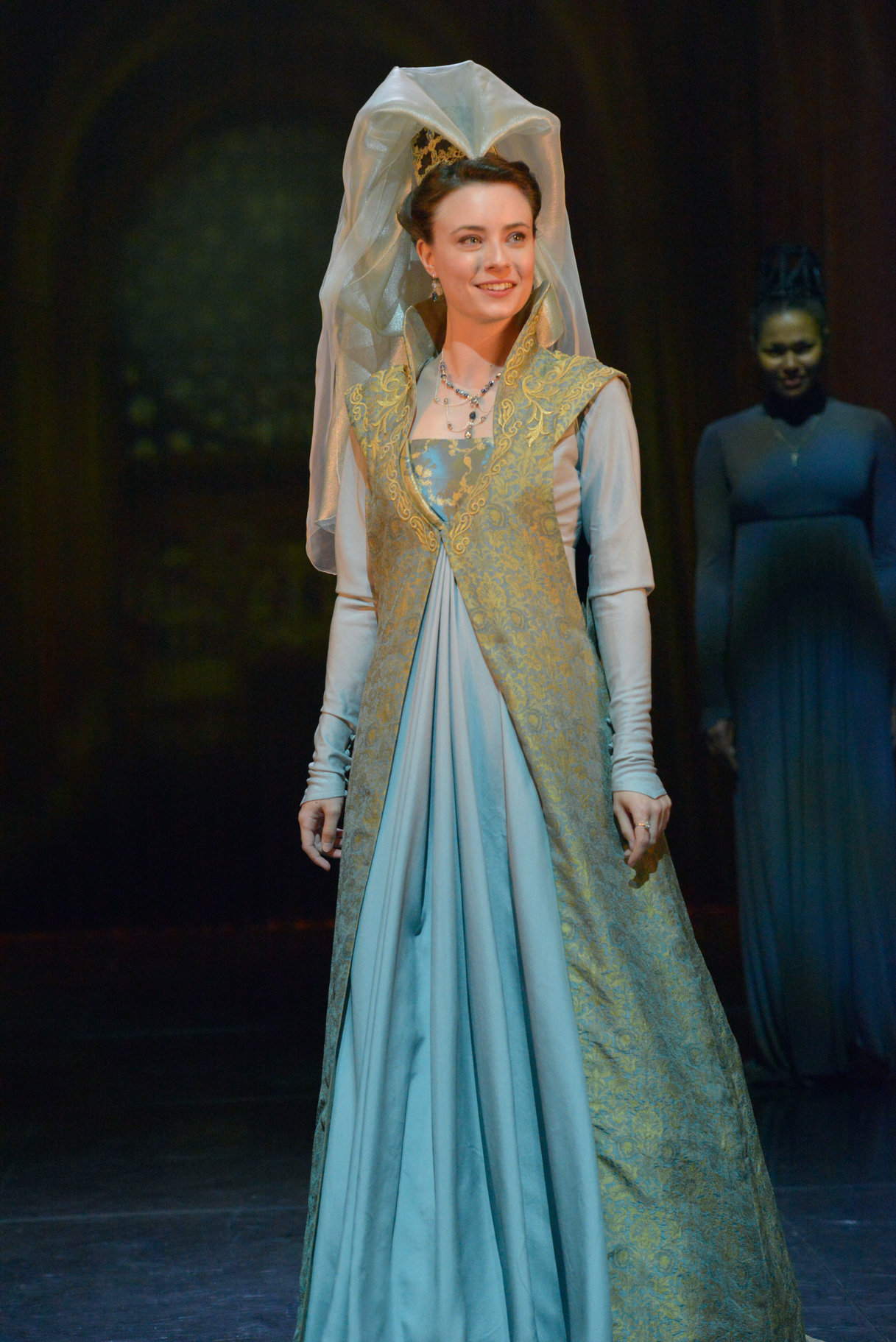 Katherine dressed in a full length blue silk dress with headdress and veil, swept back from her face, in the 2015 production of Henry V