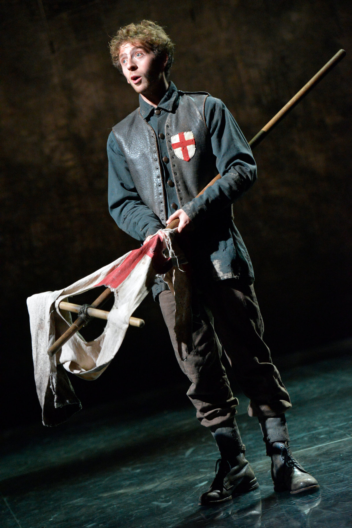 The Boy holding an English flag which has been torn, ready to speak, in the 2015 production of Henry V