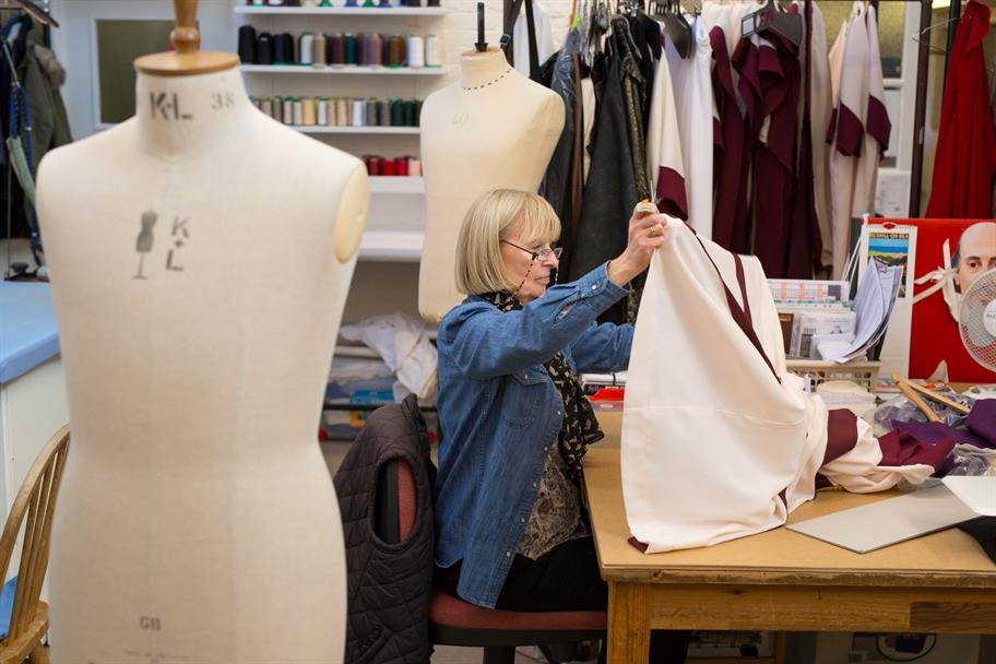 A seated woman holding up a piece of fabric she is working on, in between two tailors' dummies
