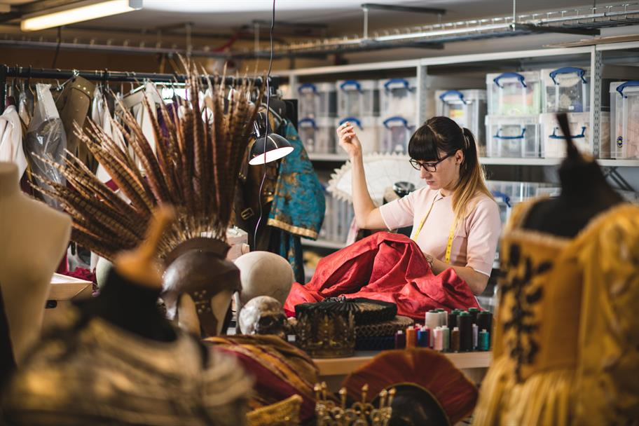 A woman with a tape measure around her neck, sewing a piece of red material, surrounded bu helmets and headdresses