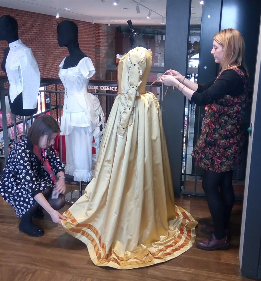 2 young women preparing a yellow dress on a mannequin