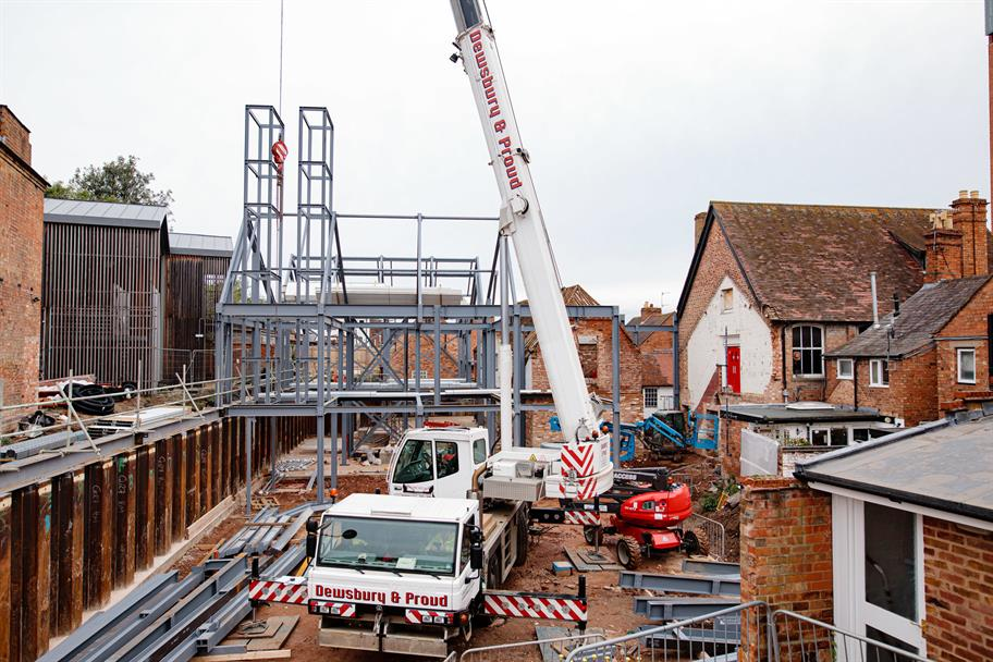A crane puts a steel building frame into place.