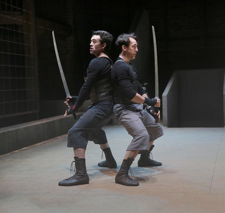 Two men leaning back to back, legs bent with swords upraised