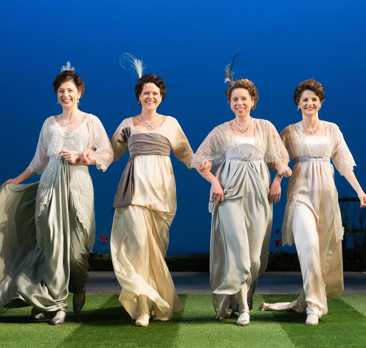Four ladies in long 1920s style light coloured gowns linking arms and striding across a lawn