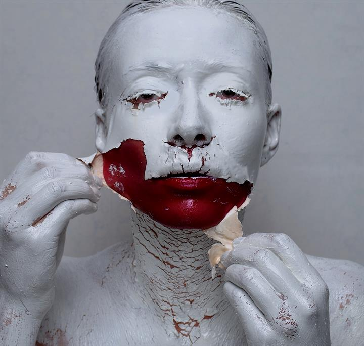 A woman rips of white clay skin, revealing dark red blood