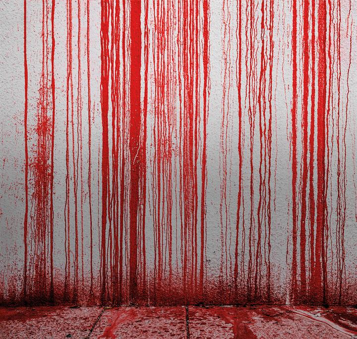 A white wall covered in red blood