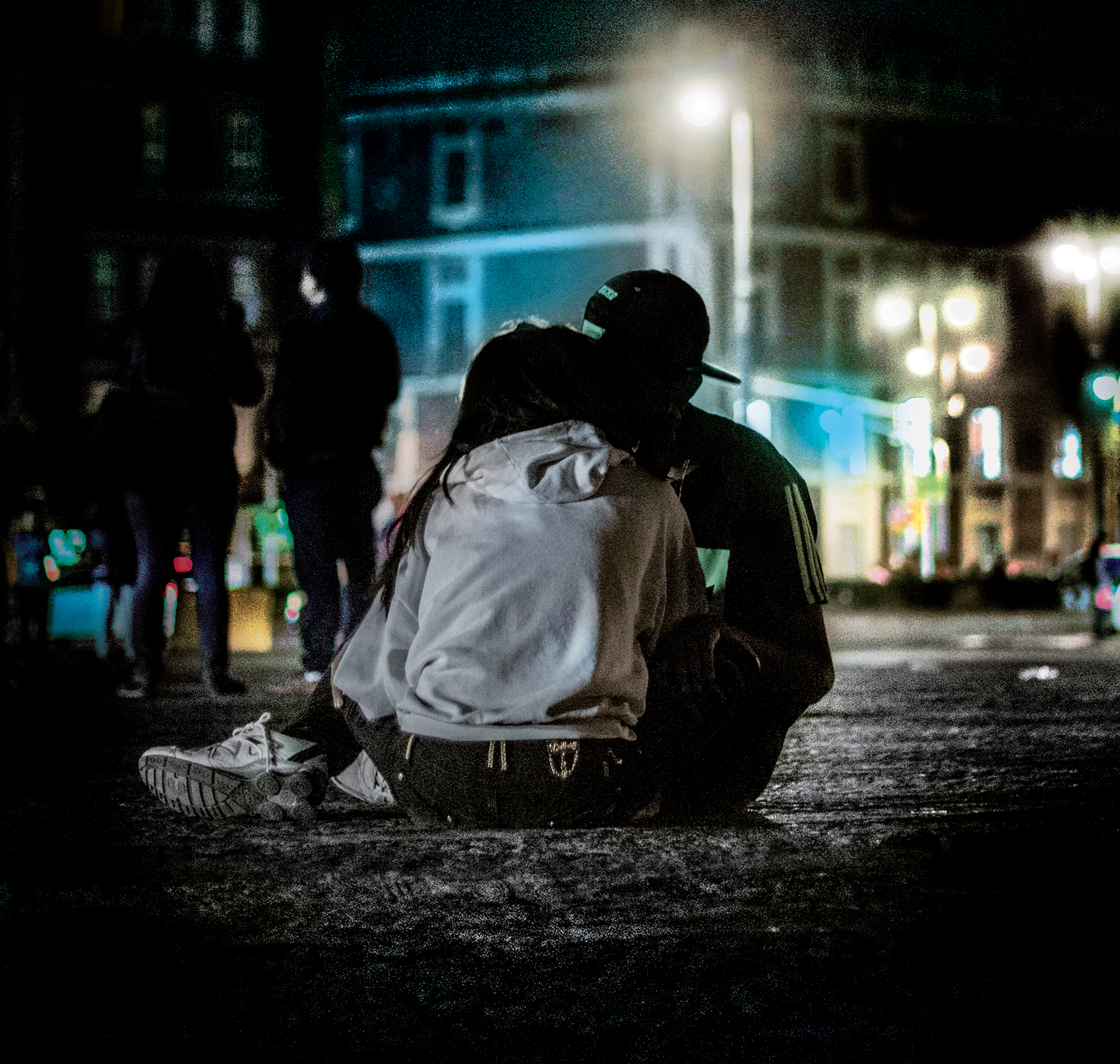 Two young adults sitting the ground kissing