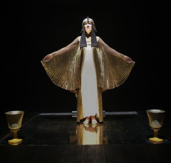 Harriet Walter on stage with arms outstretched dressed in a white and gold dress.