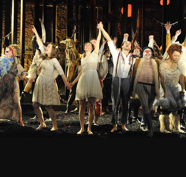 The cast of As You Like It on stage with hands raised in celebration