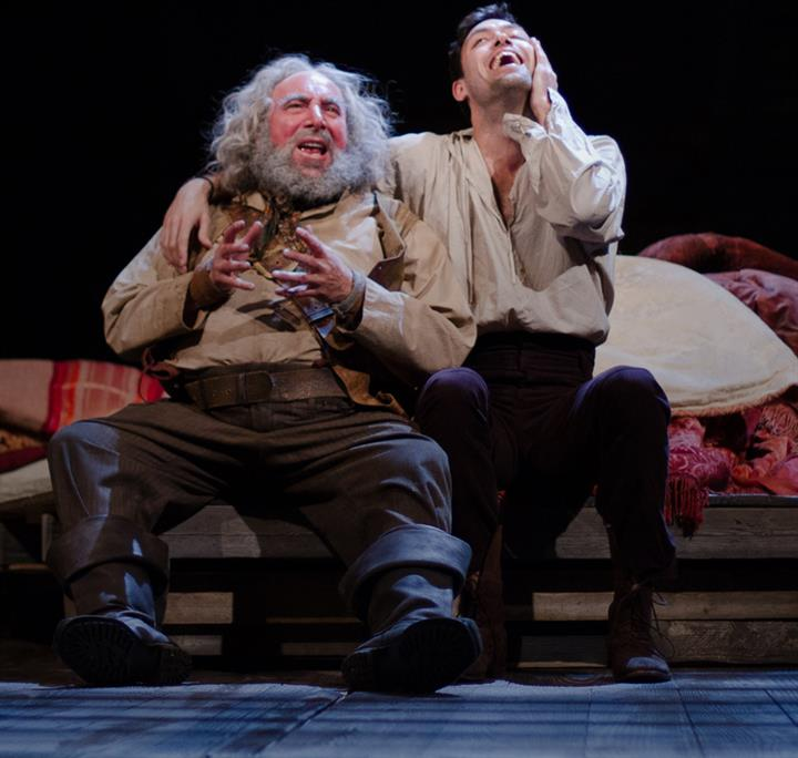Antony Sher as Falstaff and Alex Hassell as Prince Hal sit on stage talking animatedly.