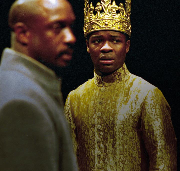 Two men on stage, one fazed out in the image, the other wearing gold robes and crown with a worried expression