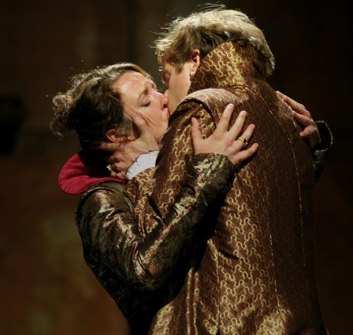 A man and woman kiss on stage