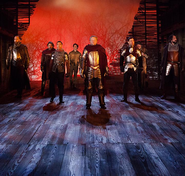 The cast stand on stage in full armour