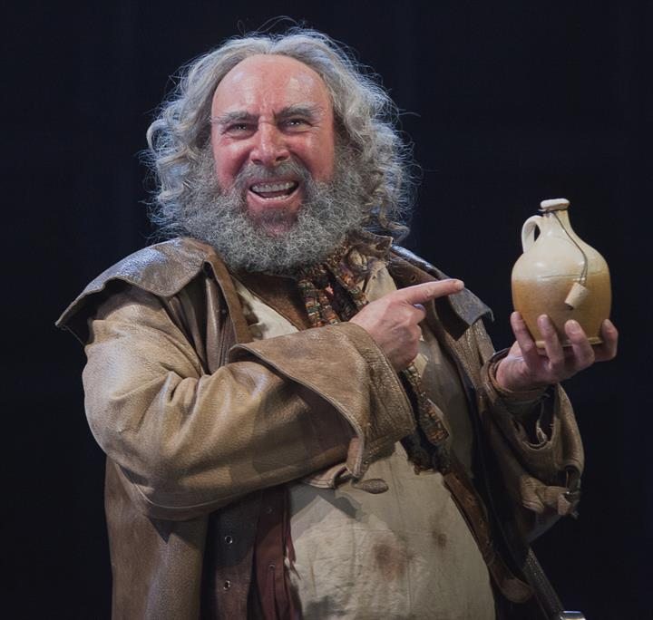 Antony Sher holds up a stoneware flask.