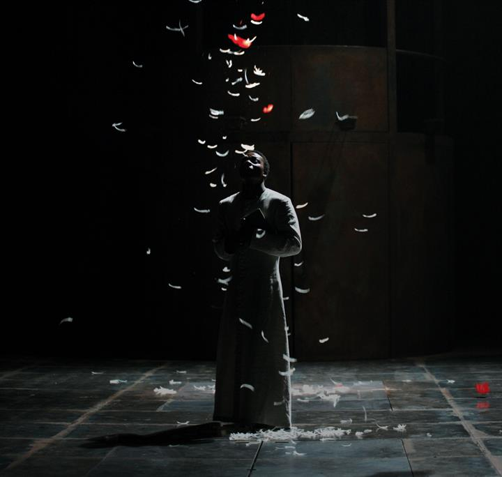 Man stands on stage silhouetted with white feathers falling overhead