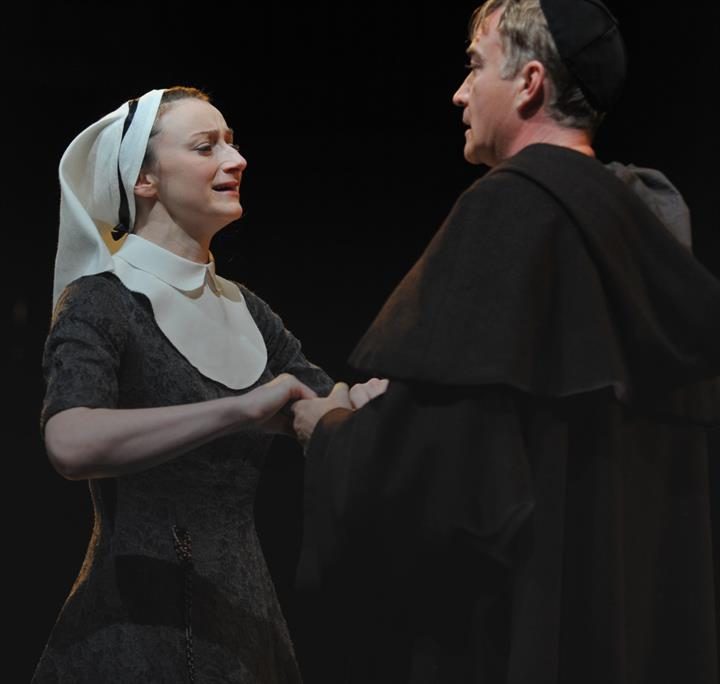 Woman and man on stage, woman looks upset