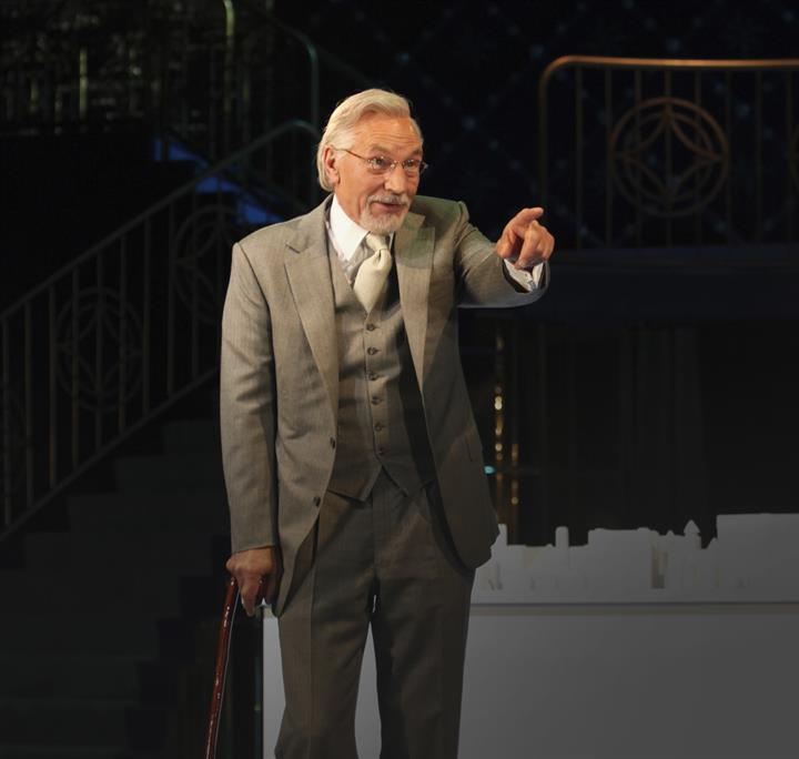 Man on stage dressed in a suit leaning on his walking stick, wearing glasses and pointing