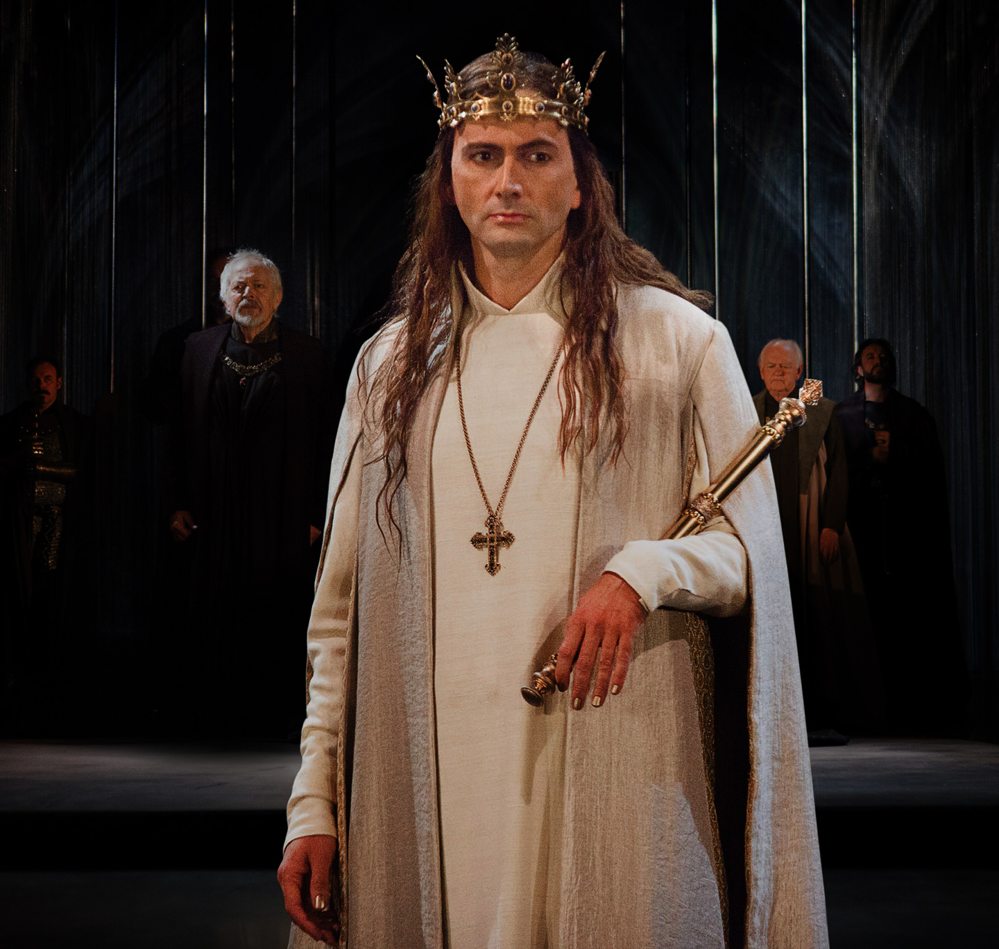 David Tennant on stage in white royal gown and crown.