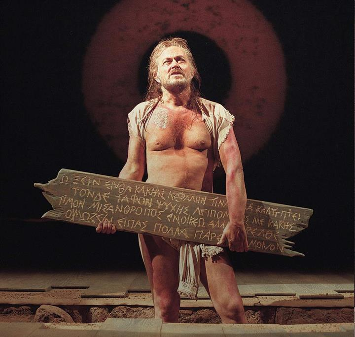 Man dressed in rags on stage holding a wooden sign