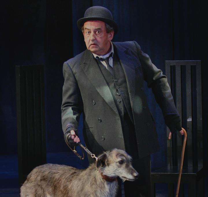 Man on stage with a dog on a leash